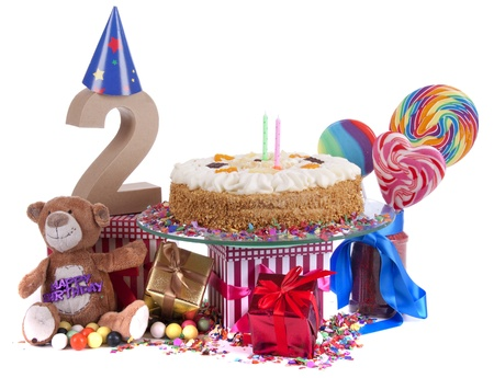 Number of age in a colorful studio setting with paper party hats, a red heart and gifts on a bottom of confetti and sweet cake with candles  photo