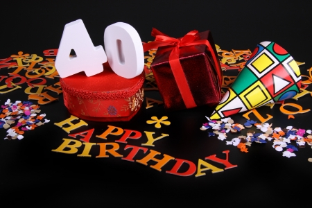 Gelukkige verjaardag op een zwarte achtergrond en een rood hart en witte caracters en confetti