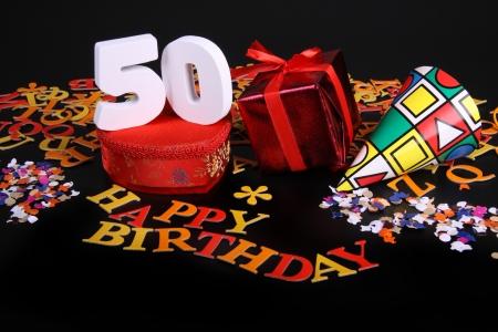 Happy birthday op een zwarte achtergrond en een rood hart en witte caracters en confetti