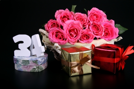 Number of age in a colorful studio setting with pink roses against a black background Stock Photo - 18291268