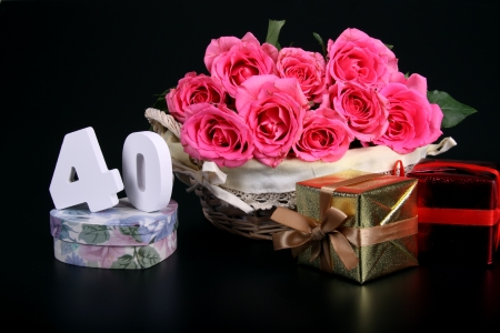 Number of age in a colorful studio setting with pink roses against a black background 写真素材