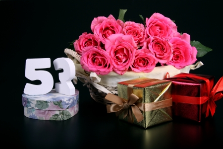 Number of age in a colorful studio setting with pink roses against a black background Stock Photo - 18291270