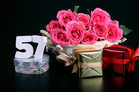 Number of age in a colorful studio setting with pink roses against a black background Stock Photo - 18291260