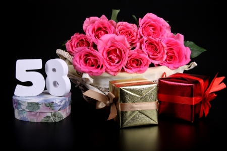Number of age in a colorful studio setting with pink roses against a black background Stock Photo - 18291274