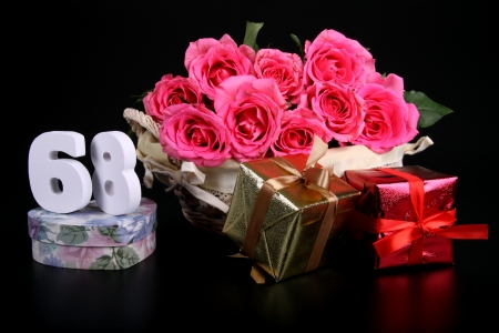 Number of age in a colorful studio setting with pink roses against a black background Stock Photo - 18291263