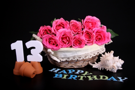 thirteen: Number of age in a colorful studio setting with pink roses against a black background Stock Photo