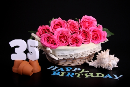 Number of age in a colorful studio setting with pink roses against a black background photo