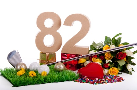 Roses, a golf club and golf balls on an artificial peace of grass to be used as a birthday card photo