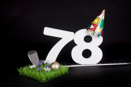 A golf club and golf ball on an artificial peace of grass to be used as a birthday card photo