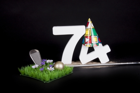 70 74 years: A golf club and golf ball on an artificial peace of grass to be used as a birthday card Stock Photo