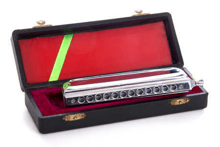 compacted: Harmonica in a box on white