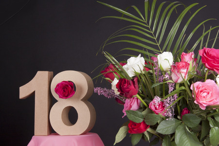 18: Age in figures next to a bouquet of flowers on a black background Stock Photo