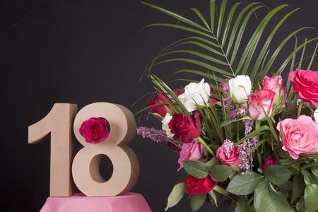 Leeftijd in cijfers naast een boeket bloemen op een zwarte achtergrond Stockfoto