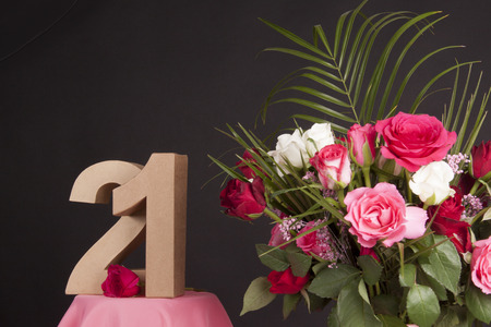 Age in figures next to a bouquet of flowers on a black background photo