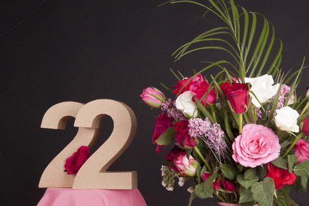 Age in figures next to a bouquet of flowers on a black background 写真素材