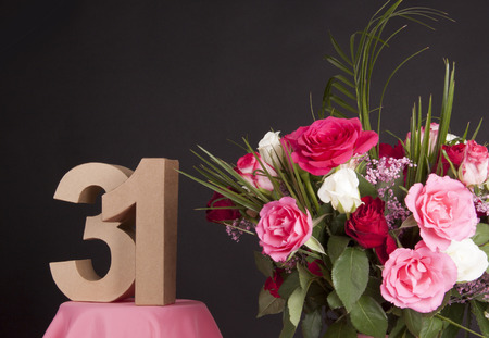 31: Age in figures next to a bouquet of flowers on a black background Stock Photo