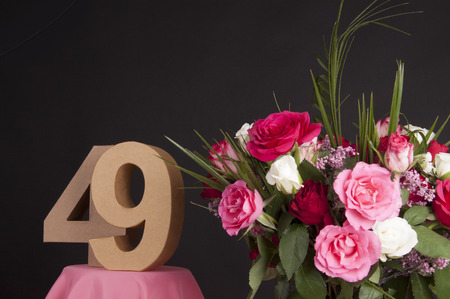 Age in figures next to a bouquet of flowers on a black background Stock Photo - 28649500
