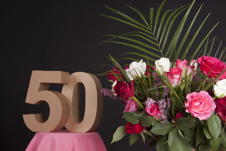 Age in figures next to a bouquet of flowers on a black background Stock Photo - 28649501