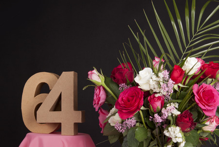 Age in figures next to a bouquet of flowers on a black background Stock Photo - 28649519