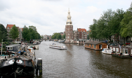 streetlife: Netherlands, Amsterdam,june 2016: The Montelbaanstoren is a tower on bank of the canal Oudeschans in Amsterdam, Netherlands. The original tower was built in 1516 as part of the Walls of Amsterdam for the purpose of defending the city and the harbour.