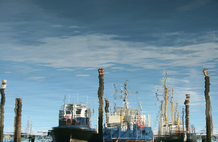 fishingboats: Netherlands, Bruinisse, july 2016: reflections of fishingboats in the harbour Editorial