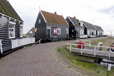 Netherlands,North Holland,Marken, june2016: Typical Marker wooden  homes on the seaside promenade of Marken