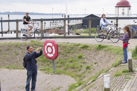 Netherlands,North Holland,Marken, june2016: Tourists photographing in the harbour district