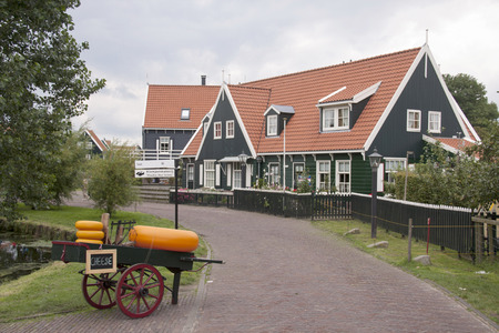 Netherlands,North Holland,Marken, june2016: Rather clumsily executed hand trolley with plastic cheeses for typical Marker homes