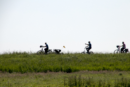 Netherlands,North Holland,Marken, june2016: bikers over the small dike of Marken