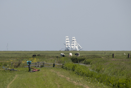 Netherlands,North Holland,Marken, june2016: meadows and rural land in the island of Marken, tall ship sailing
