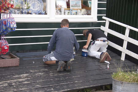 Netherlands,North Holland,Marken, june2016: Painters working on the tiny gift shop of Sijtje Boes in the port area