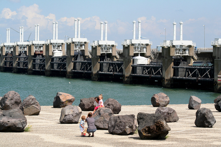 Netherlands,zeeland, Eastern Scheldt storm surge barrier july 2016: children playing with big rocks at the Former construction island the Neeltje Jans