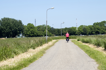 Netherlands,North Holland,Marken, june2016: biker drives in meadows and rural land in the island of Marken