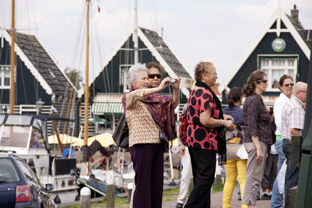 Netherlands,North Holland,Marken, june2016: Tourists in the harbour of Marken