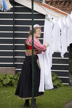 Netherlands,North Holland,Marken, june2016: eldery woman in Folk costume  does the laundry and to the camera-wielding tourists flows