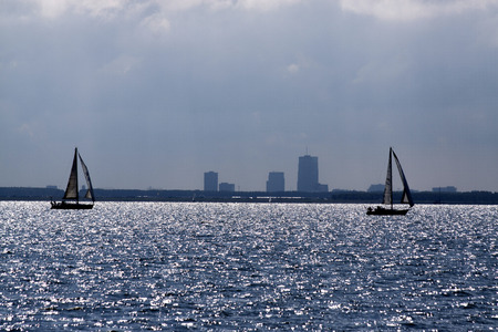 Netherlands,North Holland,Marken, june2016: Silouhet of sailboats on the Lake ' Markermeer ' with the horizon the skyline of Almere