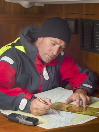 depth measurement: Sailor studying navigation chart of coastal area