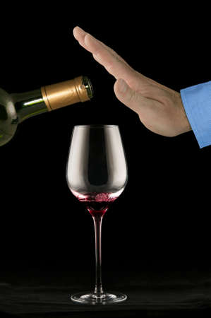 tomando vino: Sirve la mano rechazando m�s vino tinto en el vaso Foto de archivo
