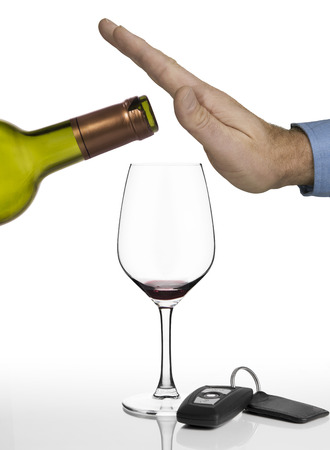 Hand of a man refusing anymore red wine and showing car keys on a white background photo