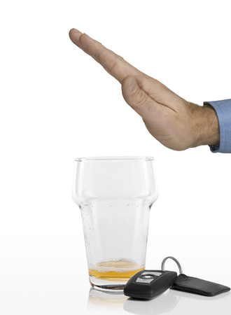 pilsener: Hand of man refusing any more beer in his empty glass next to car keys on a white background