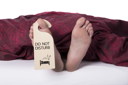 door sign: Two feet sticking out from sheets with a do not disturb label on a toe on a white background