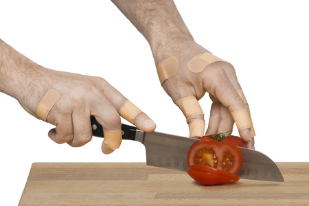 Two causcasian injured man hands with many first aid bandages slicing a fresh red tomato on a wooden cutting board