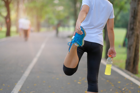 Young athlete woman streching in the park outdoor, female runner warm up ready for jogging on the road outside, asian Fitness walking and exercise on footpath in morning. wellness and sport concepts
