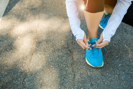 young fitness woman tying running shoes in the park outdoor, female runner running on the road outside, asian athlete jogging and exercise on footpath in sunlight morning. Sport,healthy and wellness concepts