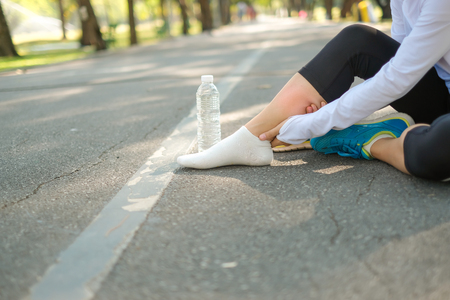 injury muscle in the park outdoor, female runner running on the road outside, asian athlete jogging and exercise on footpath in sunlight morning. Sport,healthy and wellness concepts Stockfoto