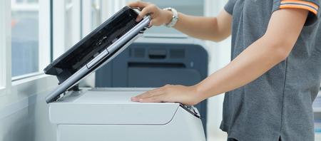 Donna di affari Mano che mette una carta del documento nello scanner della stampante o nella fotocopiatrice laser in ufficio