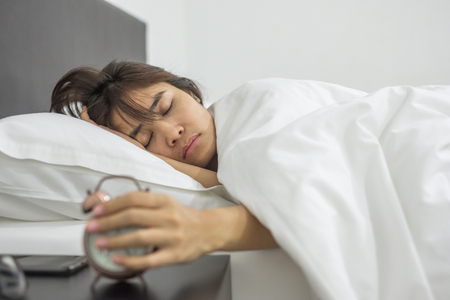 Asian woman sleeping in bed with retro alarm clock, young female lying in bedroom interior at night. Happy sleep concept