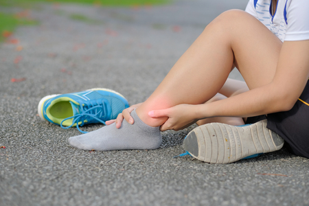 Young fitness woman holding his sports leg injury, muscle painful during training. Asian runner having knee ache and problem after running and exercise outside in summer Stock Photo - 105077568