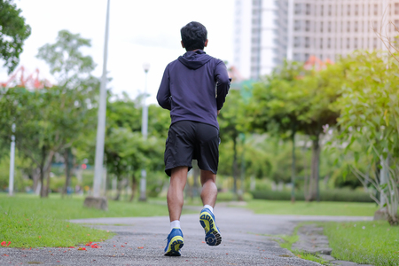 young fitness man walking in the park outdoor, runner running on the road outside, asian athlete jogging and exercise on footpath in sunlight morning. Sport, healthy and wellness concepts