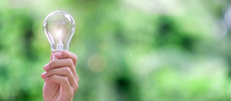 Hand holding light bulb with green background. New Idea, Creative, Genius, Innovation and solar energy concepts
